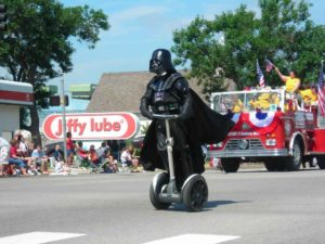 Darth Vader watching out for hoverboard fires on a Segway